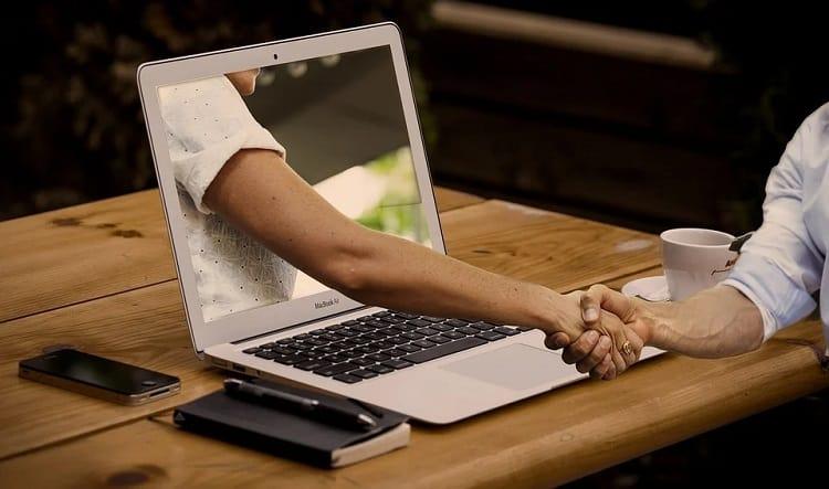 チャットボットを作る業者とパソコンを通して握手する画像